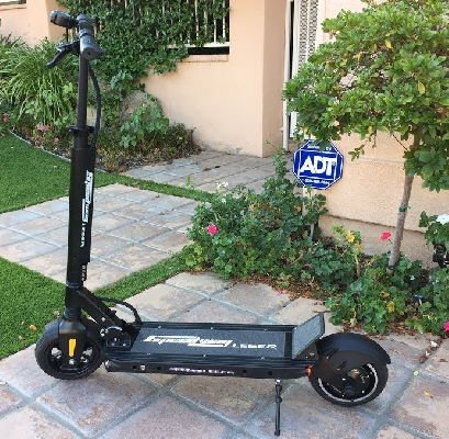 side view of a black Speedway Leger electric scooter leaning on its stand in a lawn