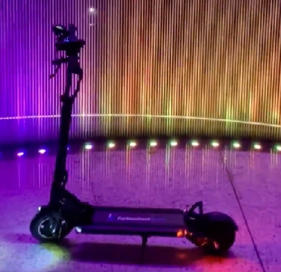 side view of a Turbowheel Swift electric scooter leaning on its stand in a room with purple lighting