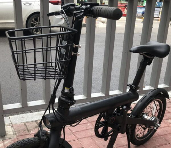 small black electric scooter with a seat and a basket in the front