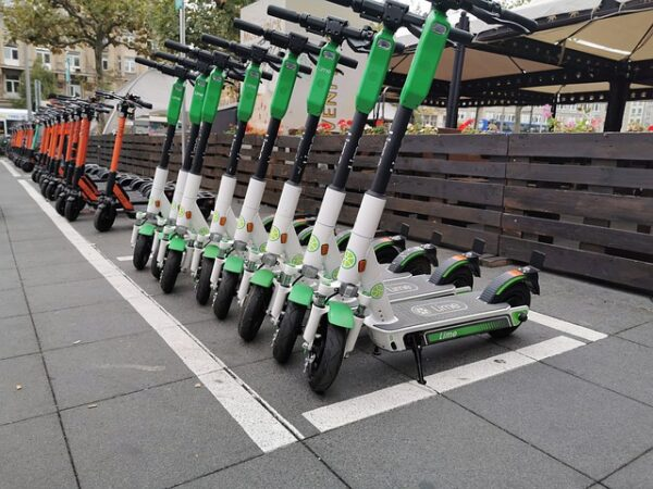 lots of rental electric scooters standing one next to another