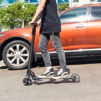 person riding a black Swagtron Swagger with an orange car in the background