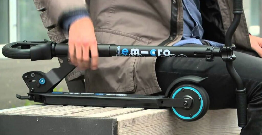 person sitting on a bench holding a folded black Micro electric scooter with blue details