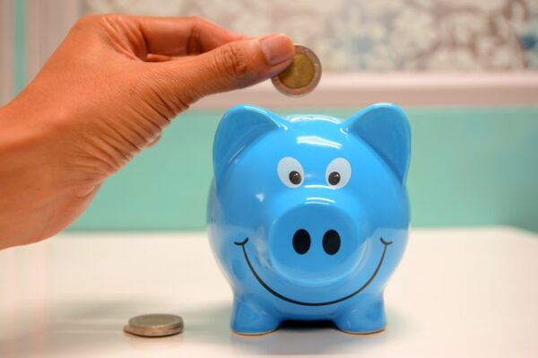 person's hand putting a coin in a blue smiling piggy bank