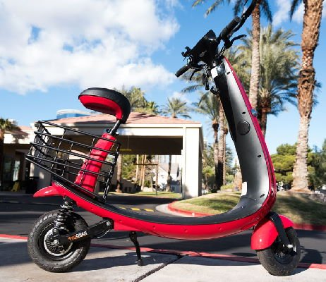 side view of a red Ford Ojo electric scooter with black details in an everyday environment