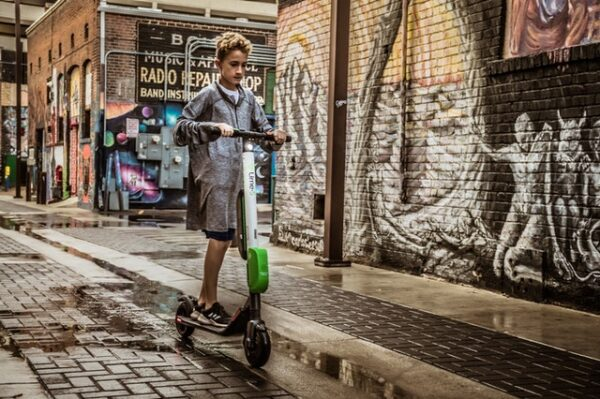 boy riding a white Lime electric scooter on a wet street in a city