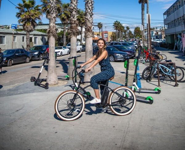girl waiting on an electric bike with several Lime and Bird rental electric scooters in the background