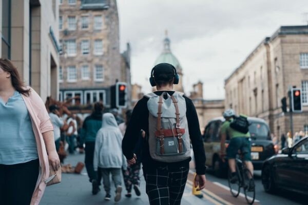person walking in a big city carrying a backpack