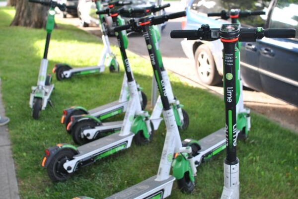 rental Lime electric scooters sitting on a grass pavement