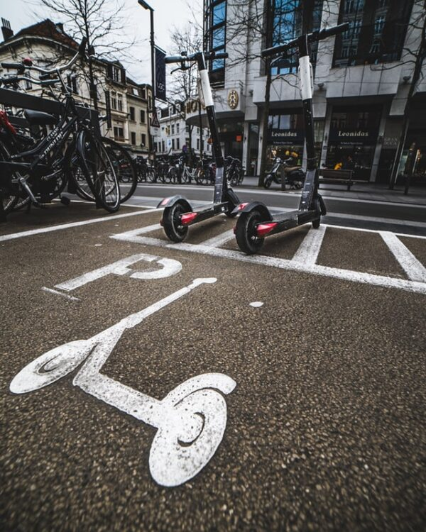 two rental electric scooters used for last mile transportation in a big city