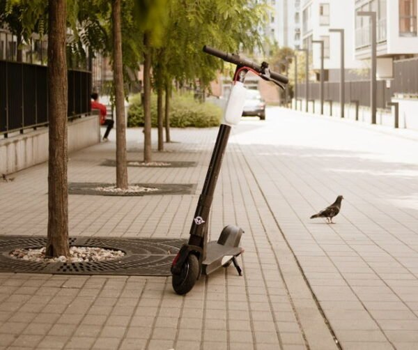 rental Bird electric scooter leaning on its stand in an urban environment