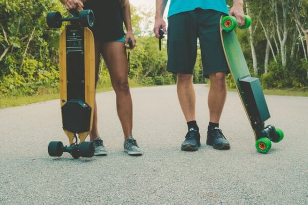 two people each holding an electric skateboard