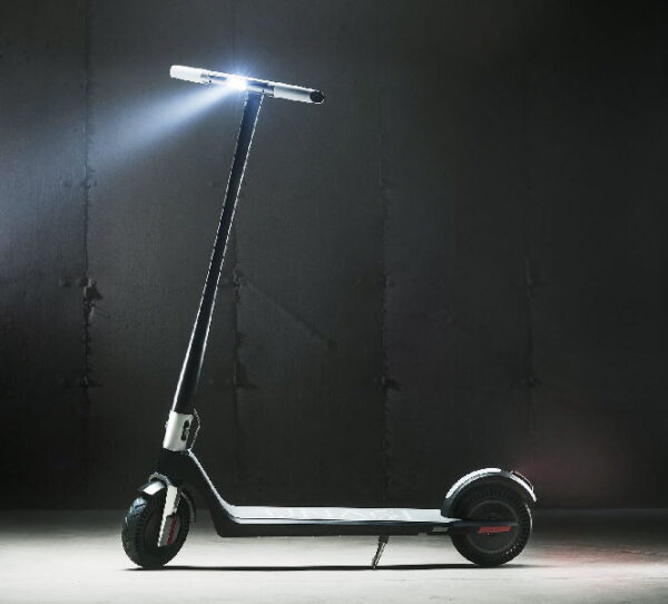 side view of a Unagi Model One electric scooter leaning on its stand with its headlight turned on in a dark room