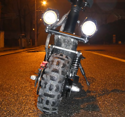 lower front part of electric scooter with two round headlights turned on and shining in the night