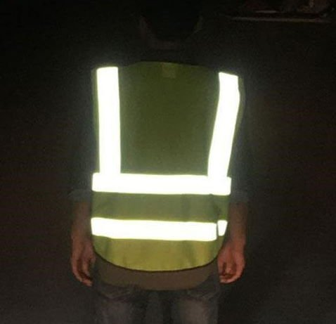 green reflective safety vest worn by a person at night