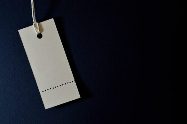 empty white perforated price tag on a dark blue background