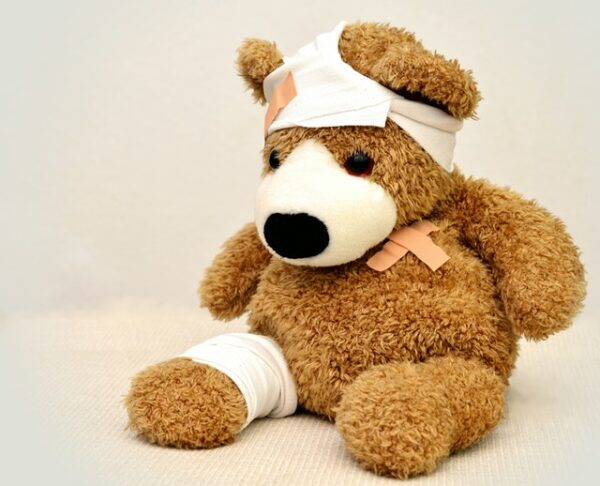 accident treated with a bandaid and bandages on a teddy bear