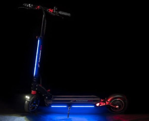 side view of a black Turbowheel Dart electric scooter with red details and many LED lights glowing in the dark