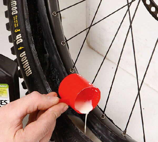 person filling a pneumatic tubeless tire with a sealant solution