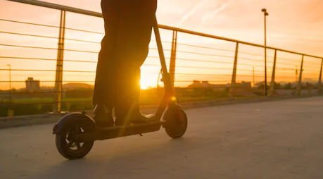 person calmly riding an electric scooter in the sunset