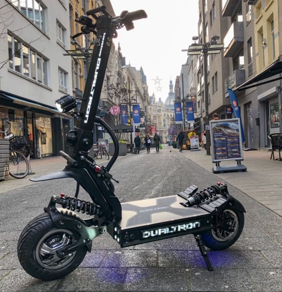 side diagonal view of a black Dualtron X electric scooter in a city walking street looking very powerful