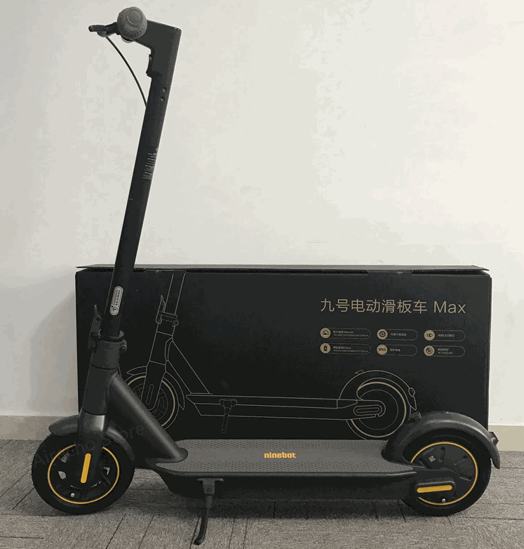 Ninebot Max leaning on its stand in a room next to its box