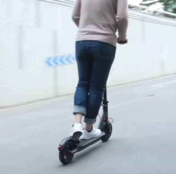 person riding uphil with an Aovo Pro electric scooter