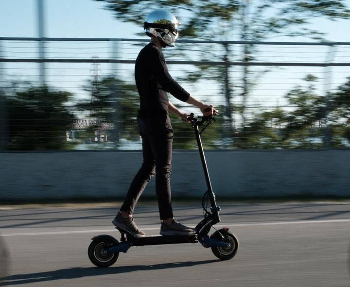 person with a helmet riding an Apollo Pro electric scooter on a street