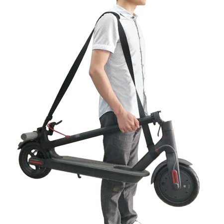 person carrying an electric scooter with a carry strap