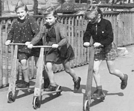 black and white photo of 3 children riding kick scooters
