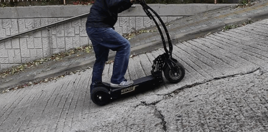 person climbing a hill on an electric scooter, leaning forward