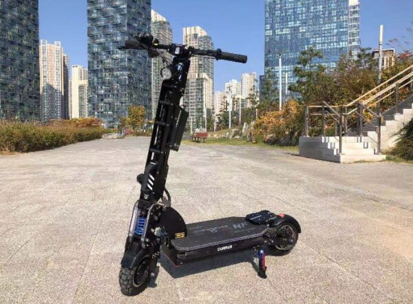 front diagonal view of a black Currus NF electric scooter leaning on its stand in an urban environment with tall buildings in background