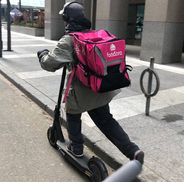 person delivering food on an electric scooter