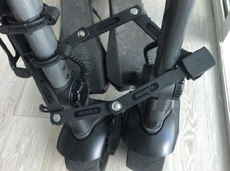 foldable lock for electric scooters around two black electric scooters