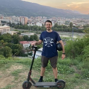 Matt standing next to his Xiaomi M365 Pro electric scooter and holding an electric scooter helmet