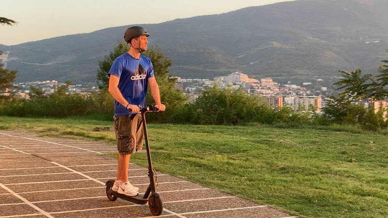 person riding an electric scooter on a sunny day