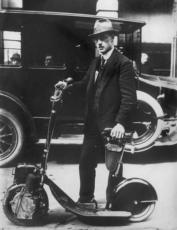 black and white photograph of a person holding a folding motorized scooter