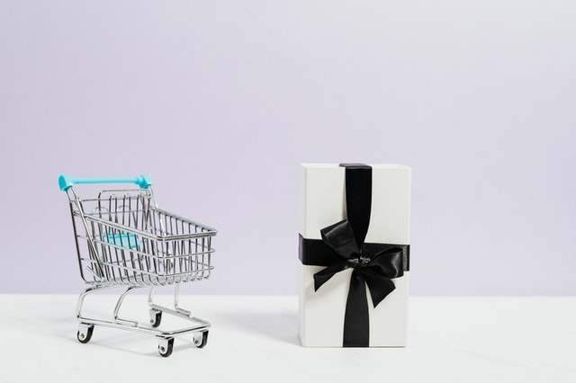 a large wrapped gift next to a shopping cart