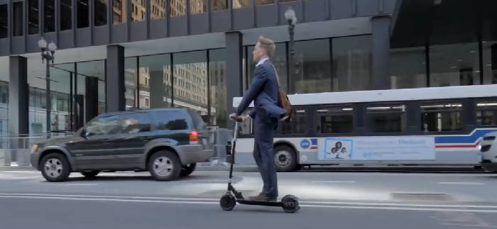 person commuting on a Glion Dolly in an urban setting