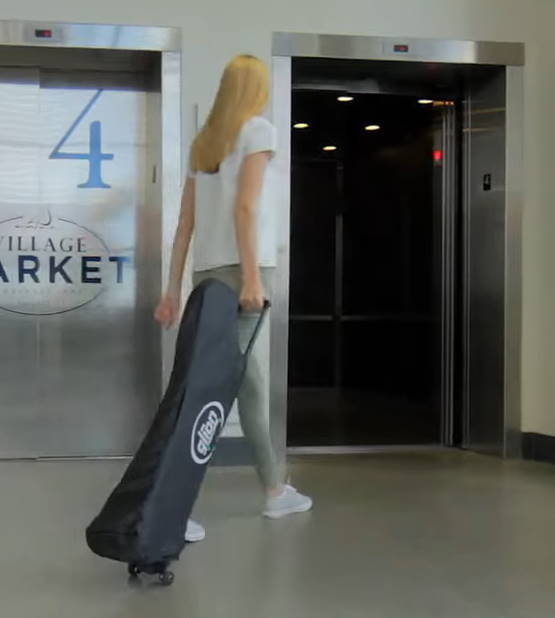 person pulling a folded Glion Dolly scooter into an elevator