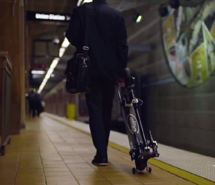 person pulling a folded Glion Dolly in a train station