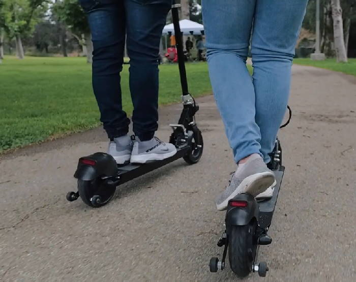two people riding Glion Dolly scooters