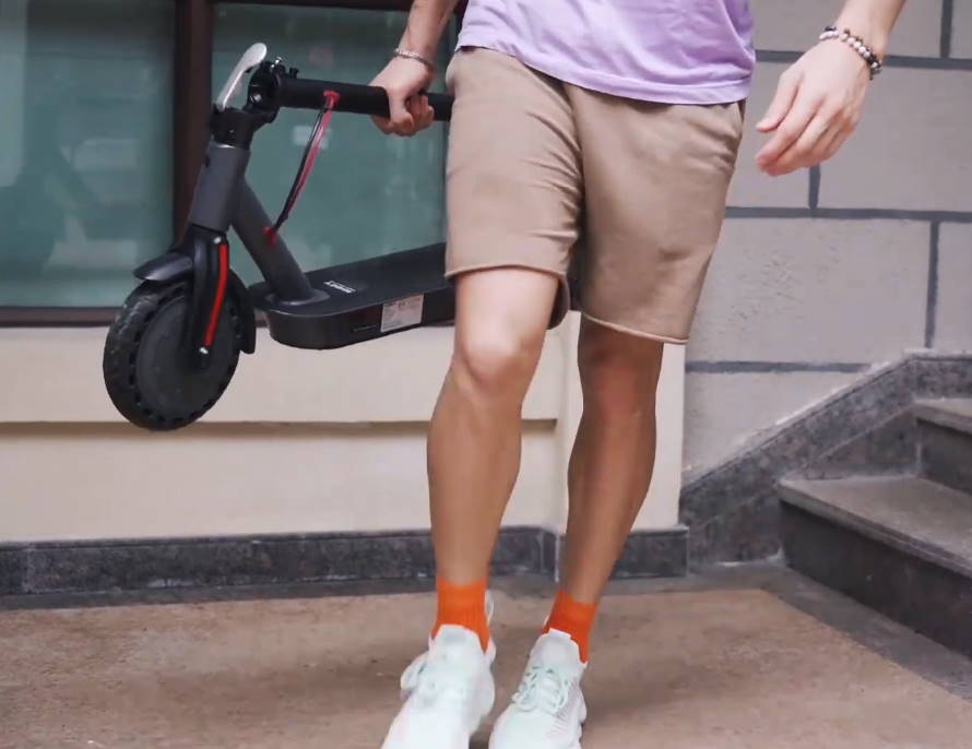 person carrying a folded Hiboy S2 scooter