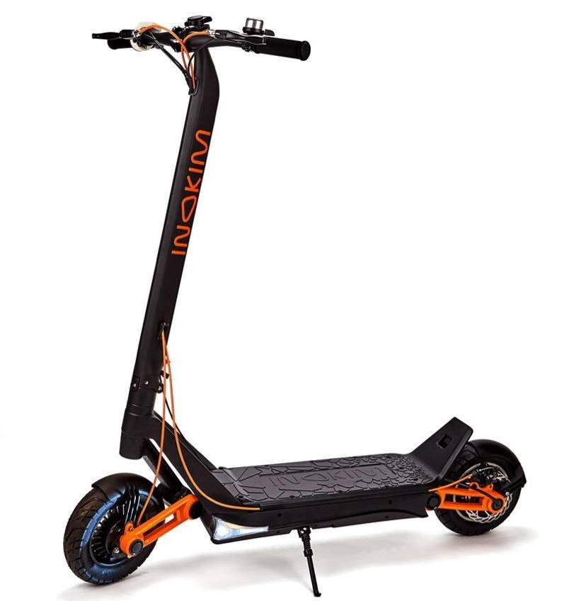 side view of the Inokim OX electric scooter with orange details leaning on its stand on white background