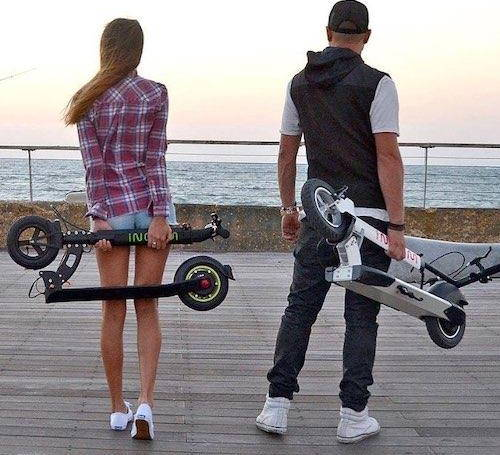 a woman and a man carrying folded Inokim Light 2 electric scooters