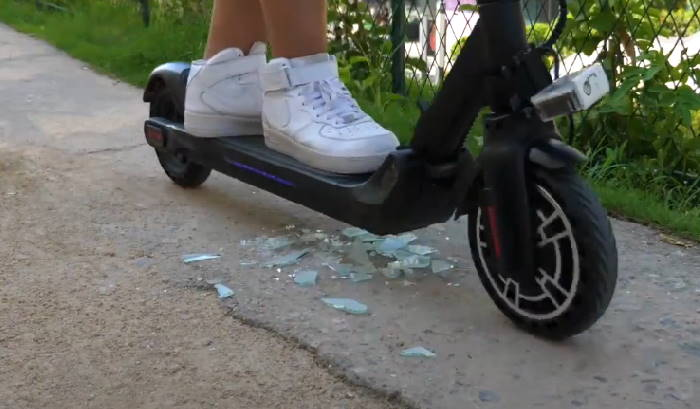 tires of the Kugoo ES2 riding over broken glass