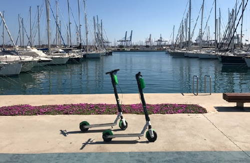 two Lime rental electric scooters on a dock