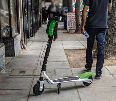 a Lime scooter leaning on the sidewalk