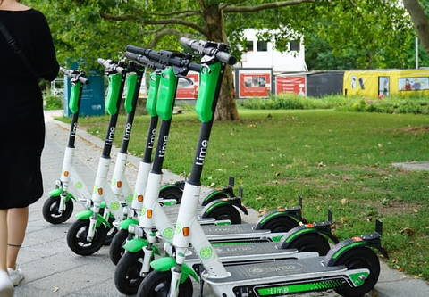 several Lime rental electric scooters parked on a sidewalk