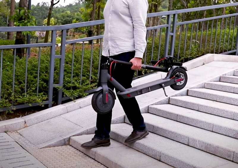 person carrying a folded Macwheel MX Pro on stairs