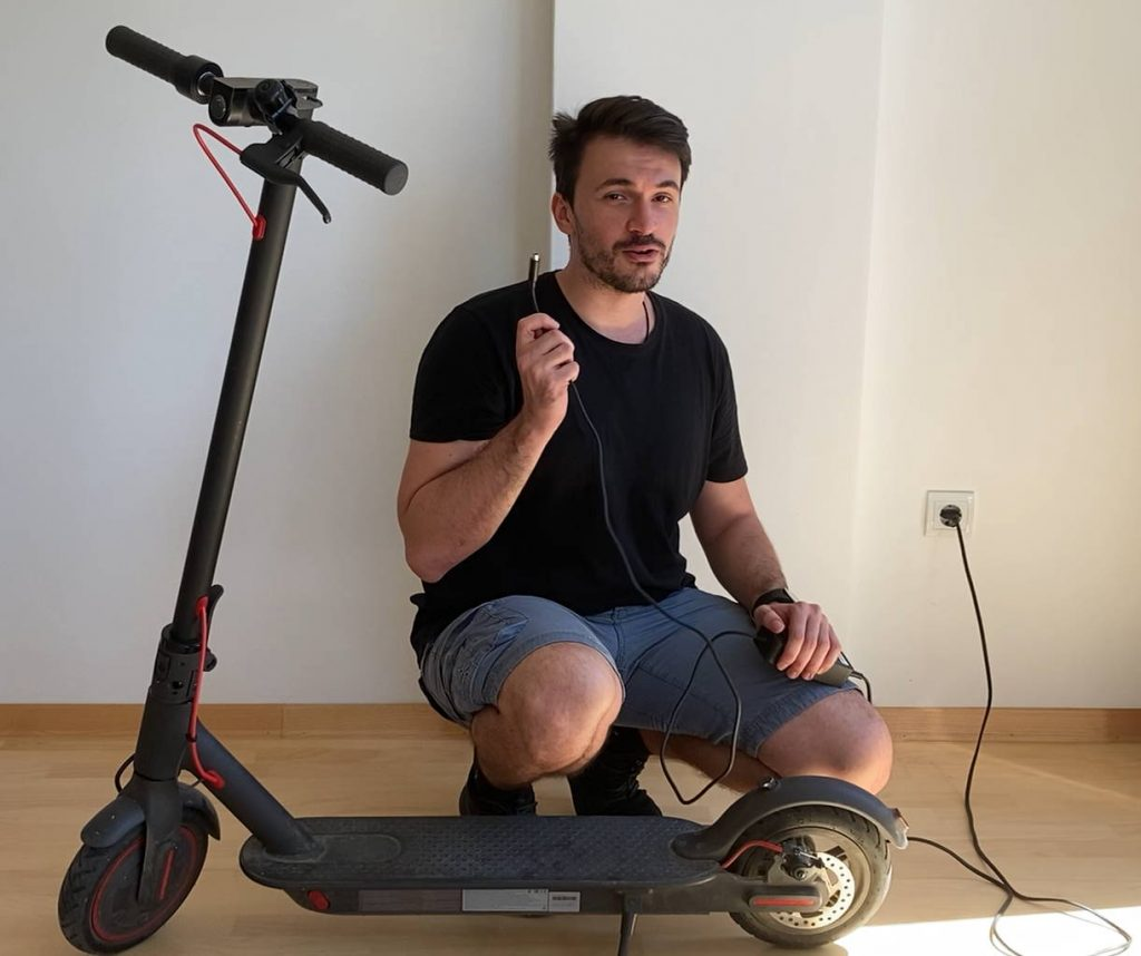 person showing how to charge an Xiaomi M365 Pro electric scooter